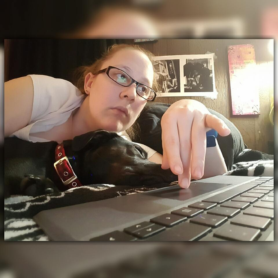 Online freelance writer with her dog beside her napping
